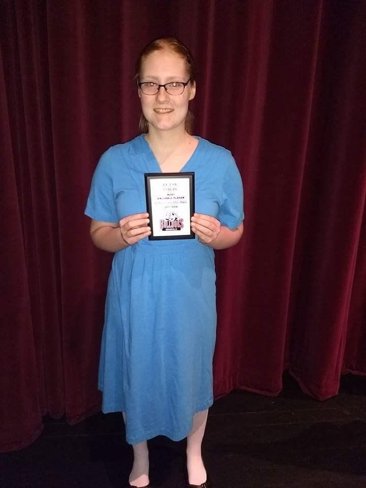 girl holds award