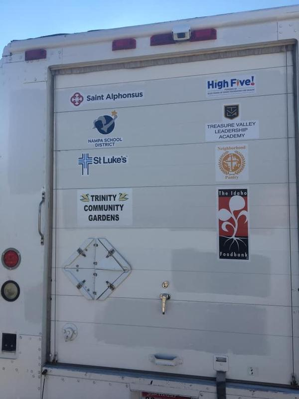 Logos for Traveling Table sponsors, shown on the back of the delivery truck.