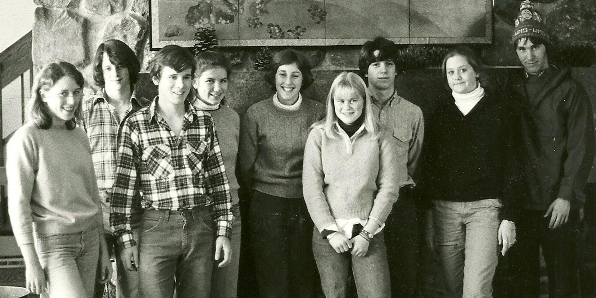 A vintage photo of students standing in front of the stone fireplace in McLane Building.