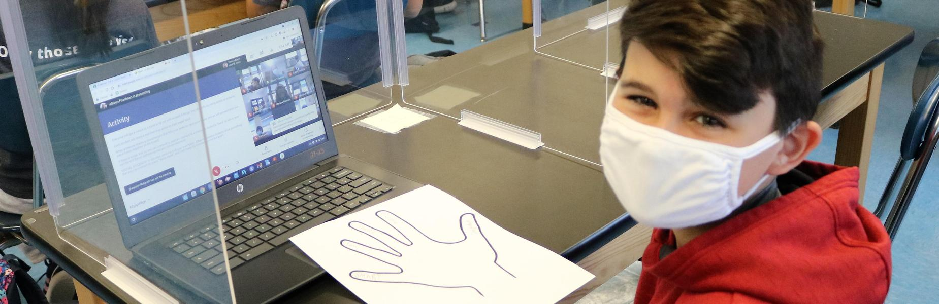 Photo of Edison student with hand print cut out as part of Cultural Diversity Day