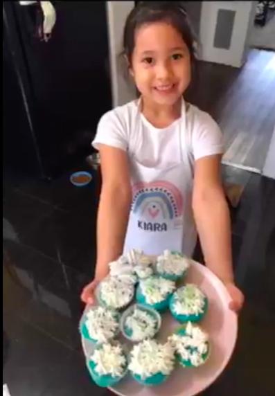 Girl holding platter of cupcakes
