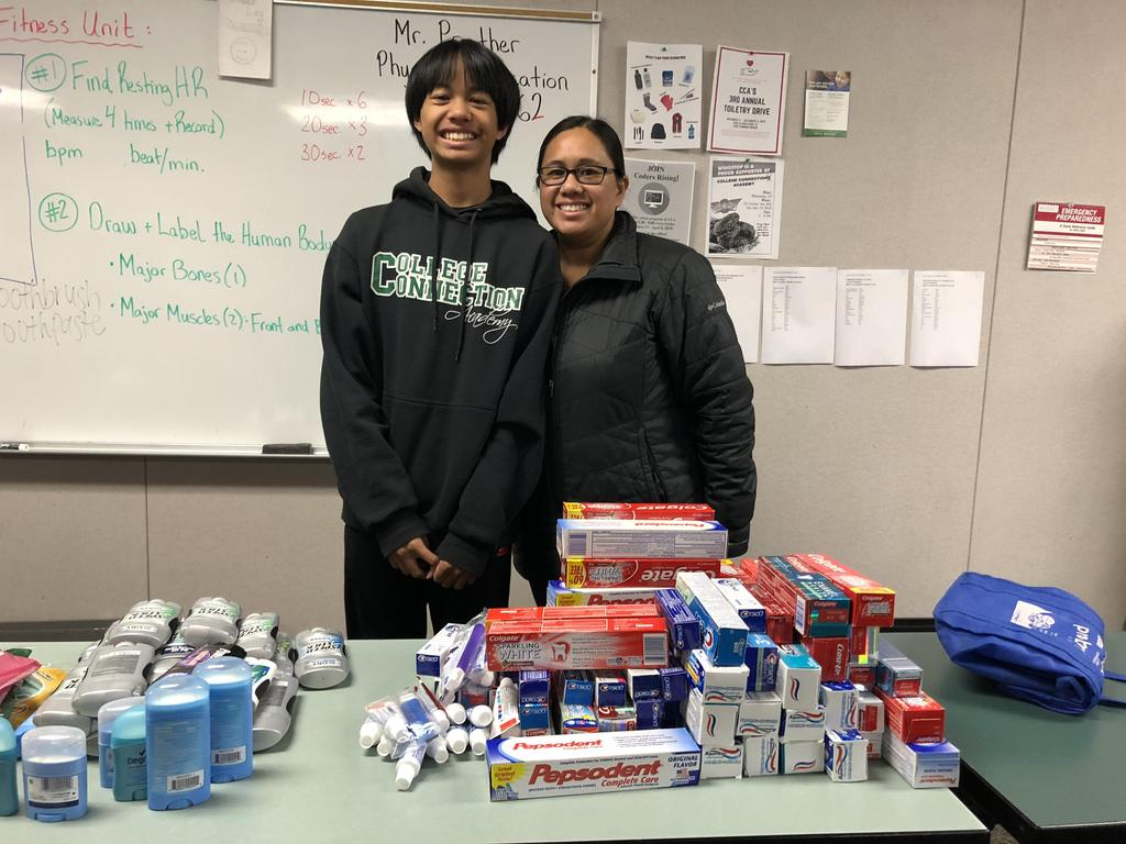Two CCA volunteers standing behind a table full of toiletries.