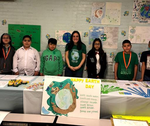 Green Team Teacher Lead and student members posing for picture behind display table.