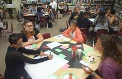 DVMS teachers gather at a meeting in the school library to discuss teaching  strategies.