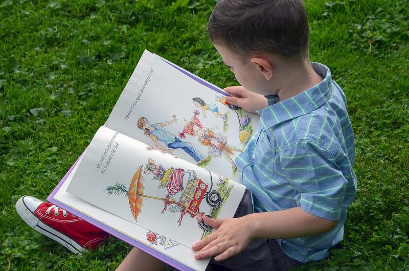 the image is of a young boy in a blue shirt and red sneakers sitting in green grass and reading a picture book