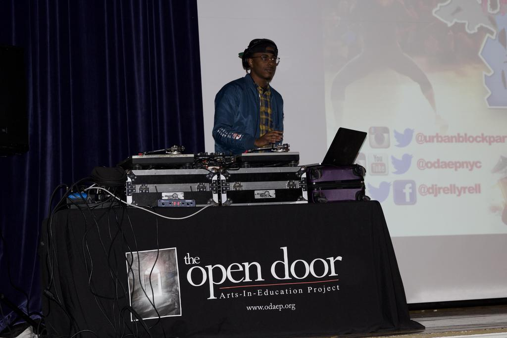 Man behind DJ equipment showing slideshow presentation