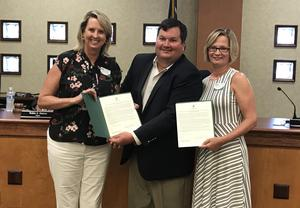 Mary Brooks, left, Director of Parenting / Early Childhood Coordinator, and Christy Henderson, right, Director of Adult Education, receive a resolution from Mayor Pro Tem Tem Miles.