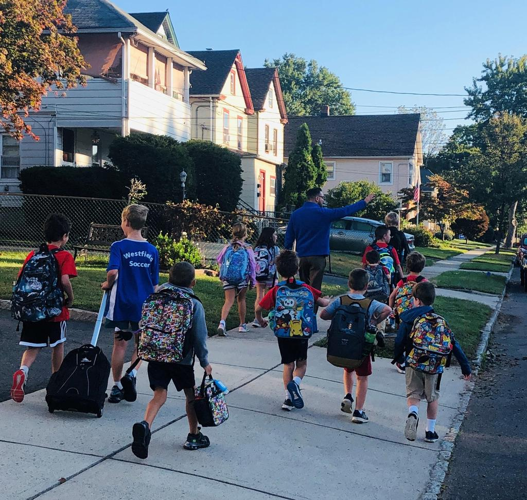 Photo of McKinley principal Dr Marc Biunno with students on Walk to School Day.