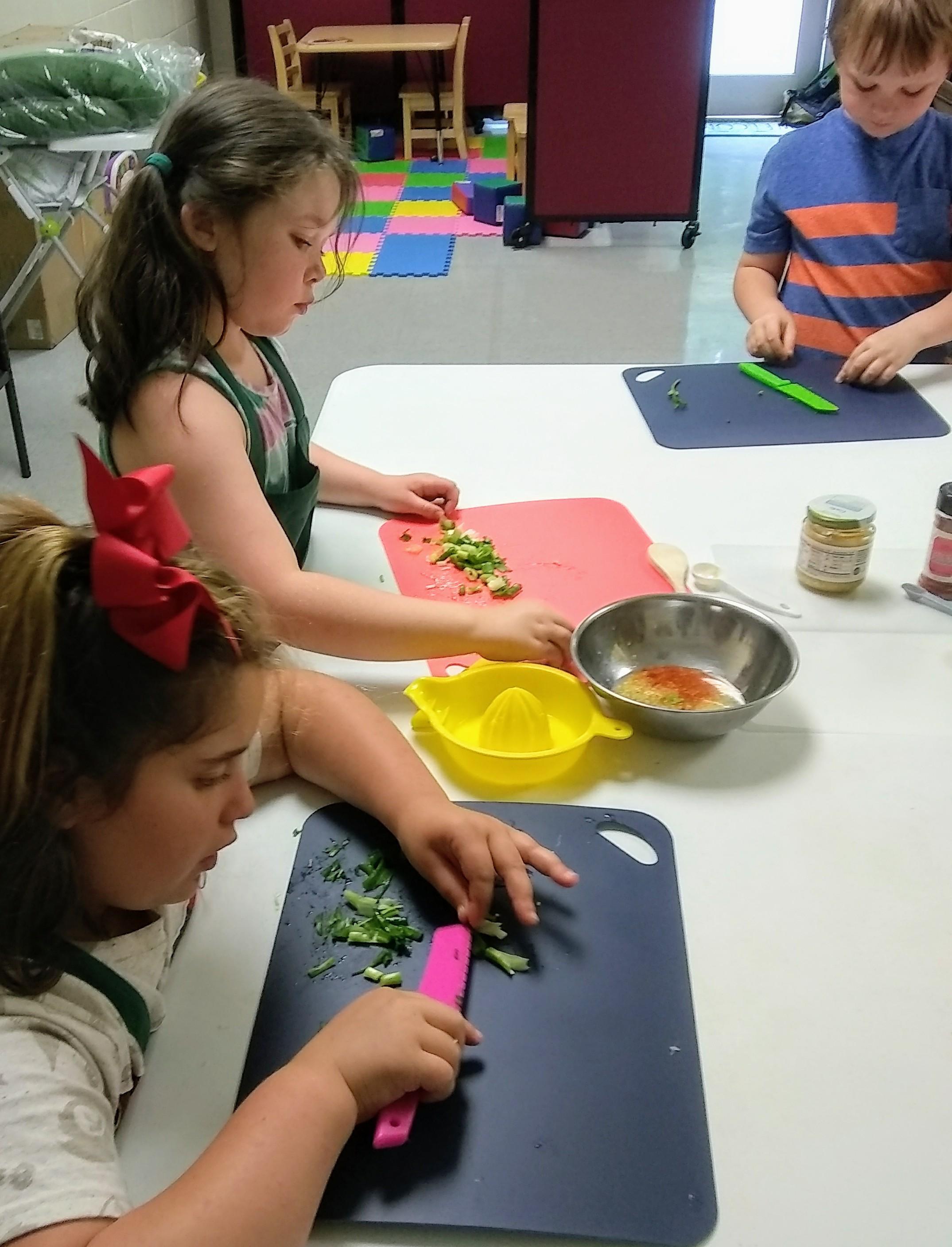 kids juicing limes for salad dressing