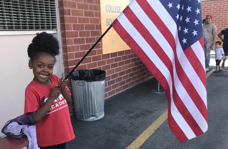 student holding US flag
