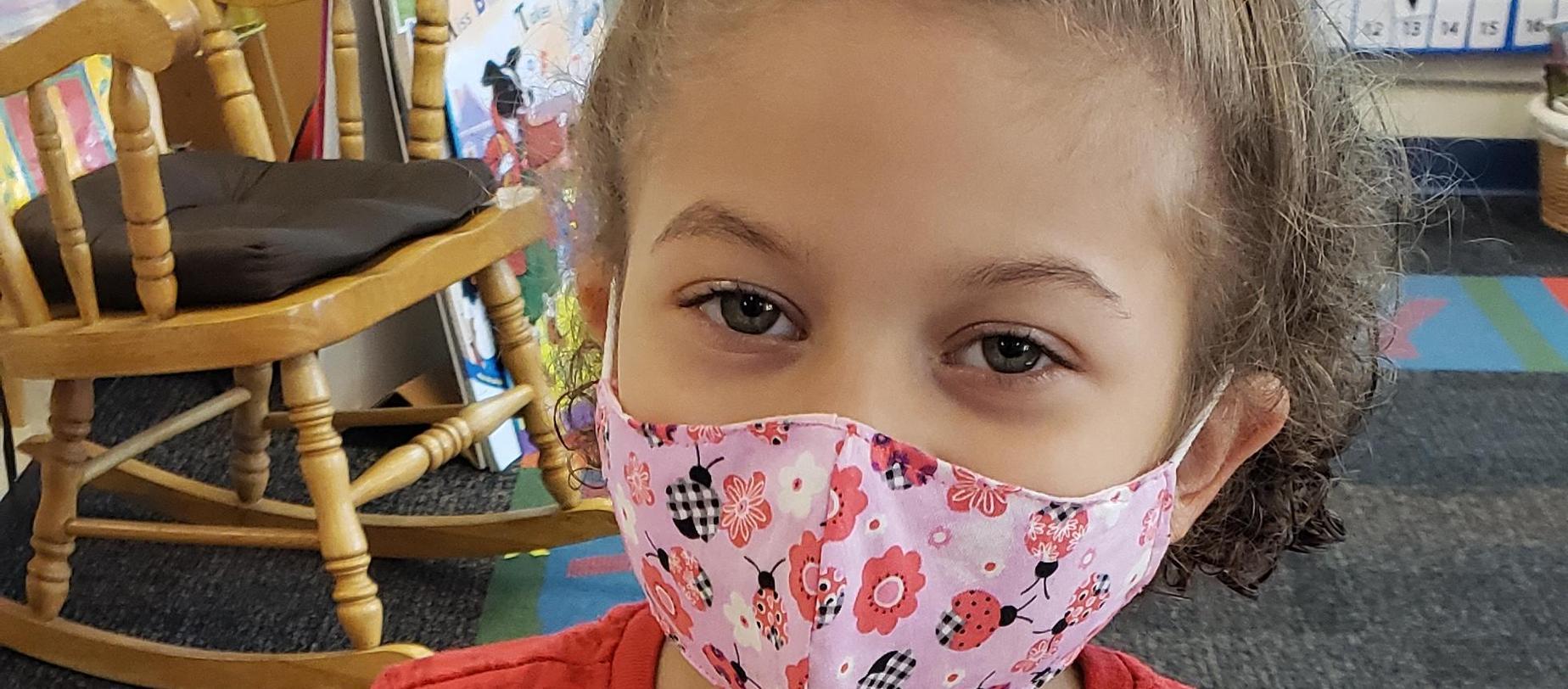 girl in mask posing for camera