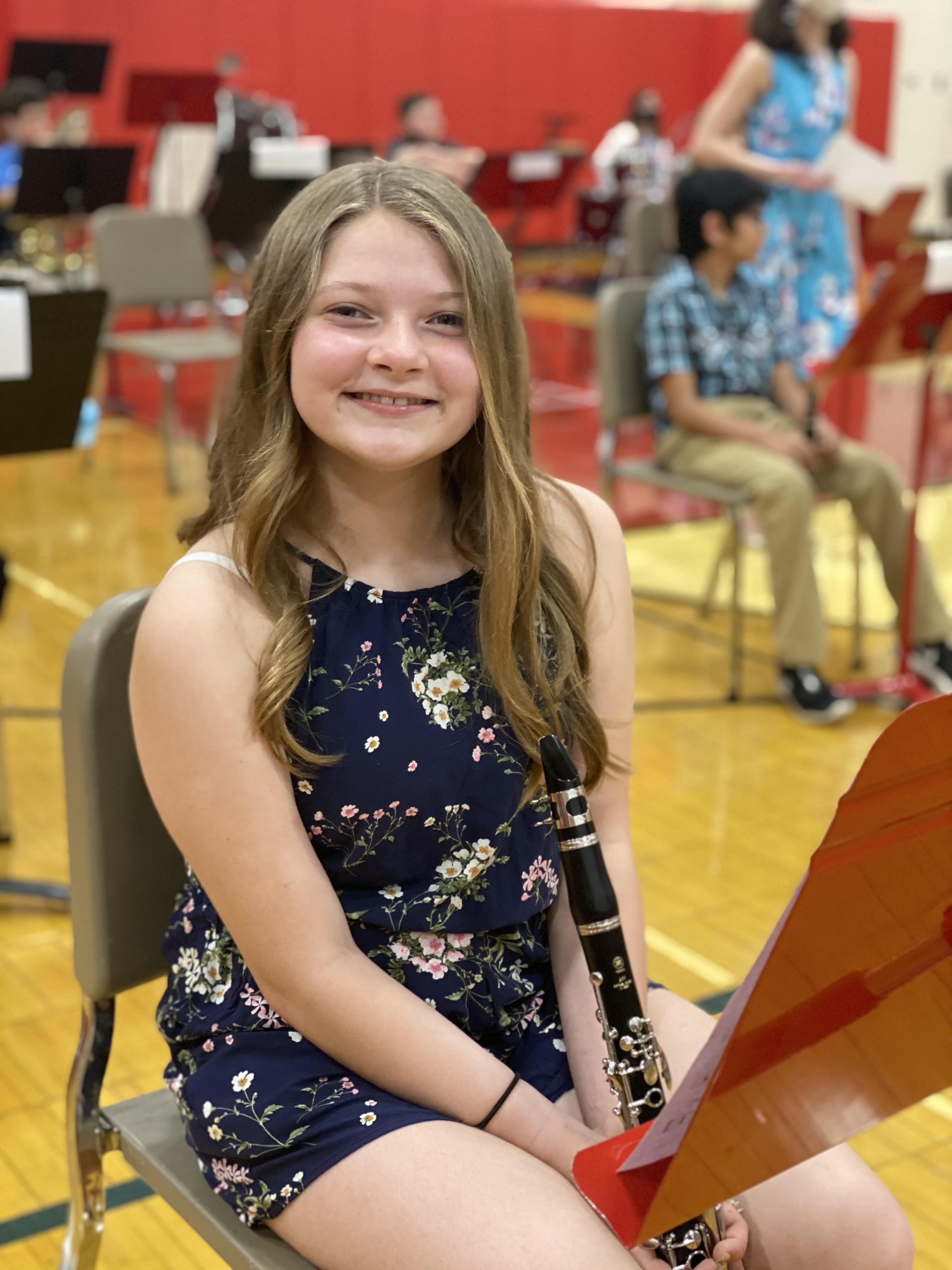 A student holding a clarinet and smiling at the camera