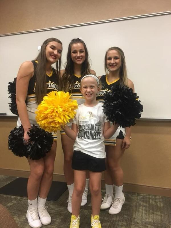 MCES Student standing with three Appalachian State Cheerleaders