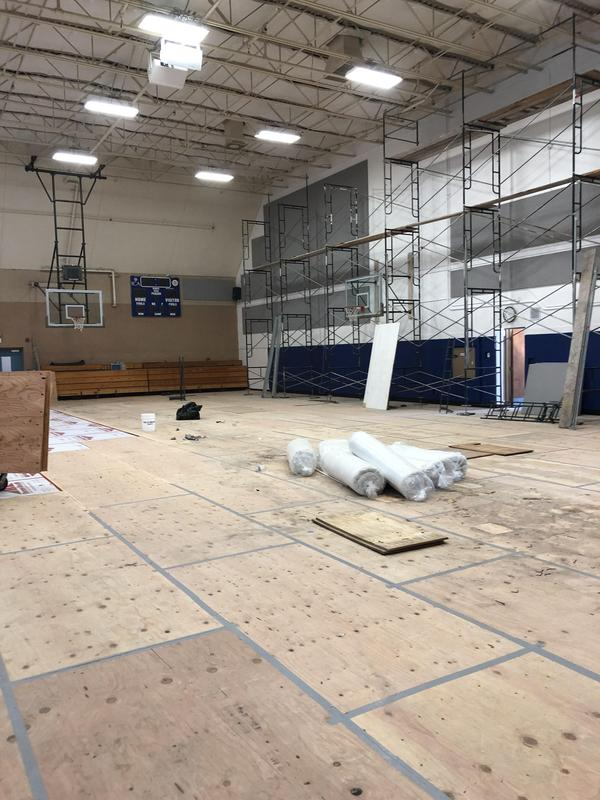 Gym floor covered in protective plywood. Other rehab supplies seen too.