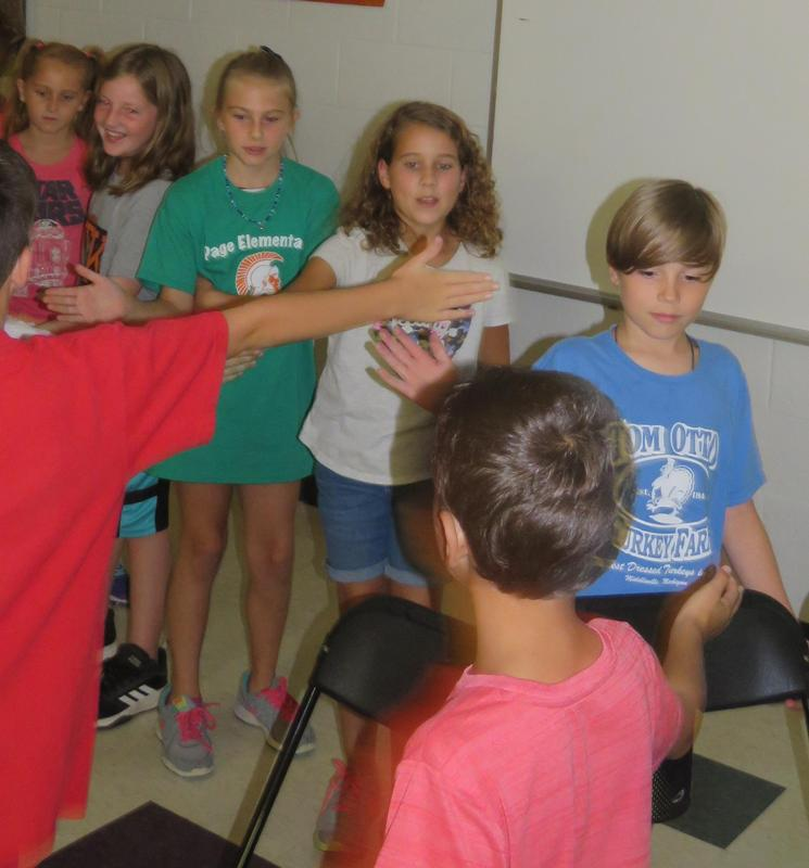 Students give each other fist bumps and high 5's after their character assembly.