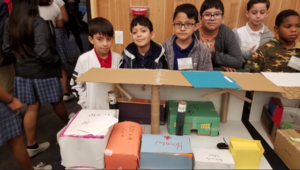students pose with project