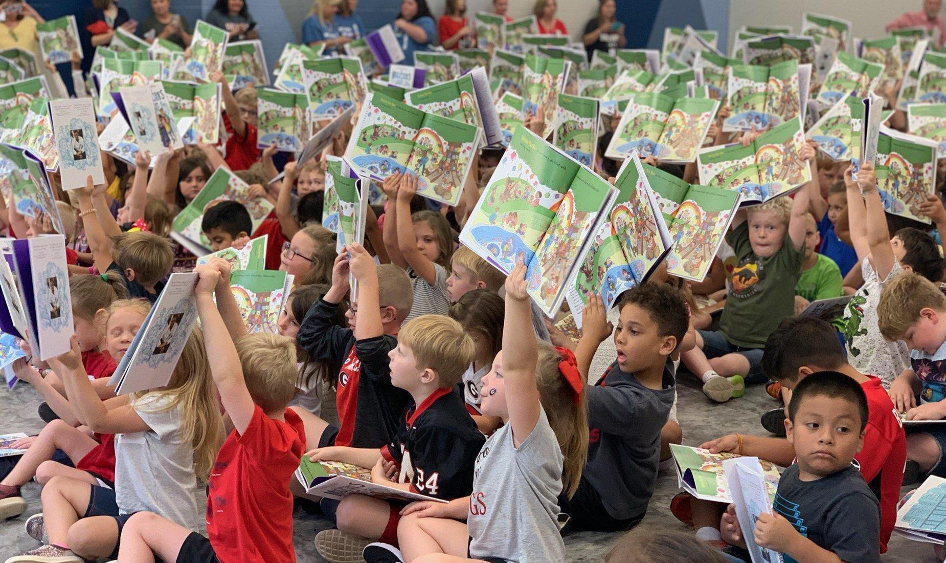 Students sitting holding up books