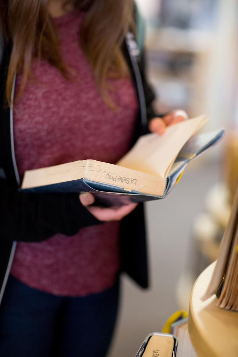 student holding a book open