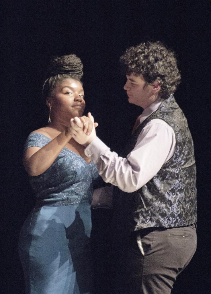 Two actors dance, hand in hand