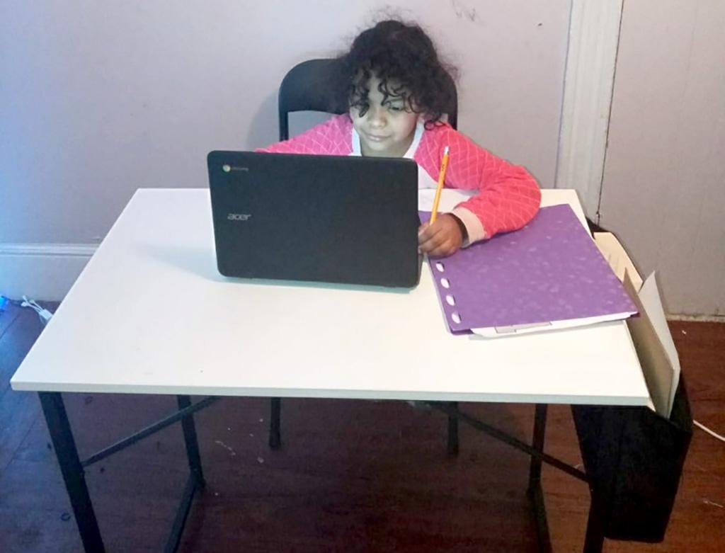 A view of a student working at desk and laptop