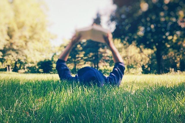kid reading on grass