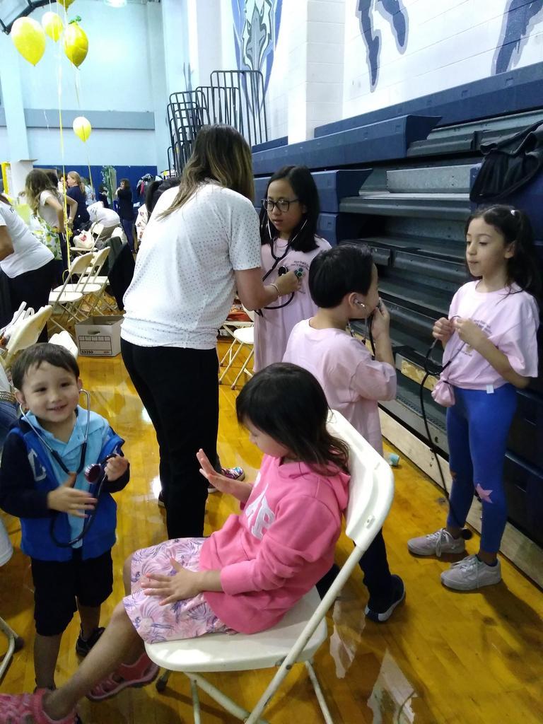 group of kids holding onto stethescopes