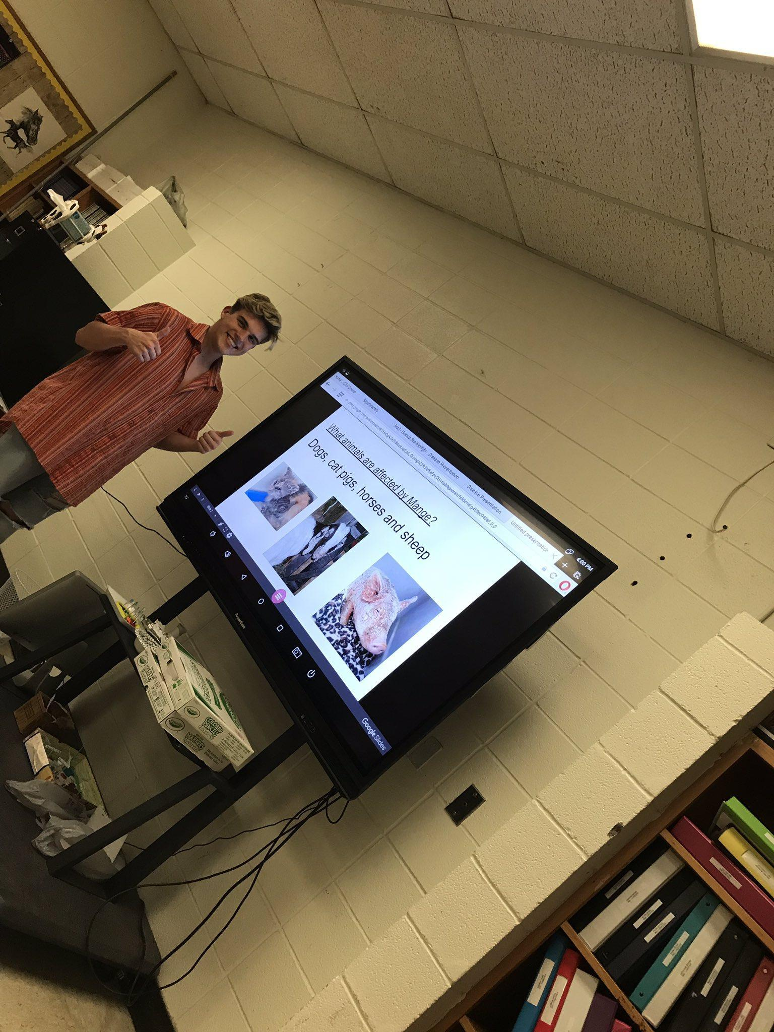 student in front of tv screen presenting on Mange