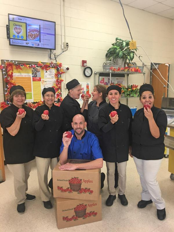 school nutrition staff biting apples