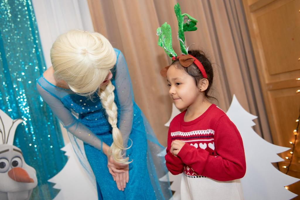 """Elsa from """"Frozen"""" leans over as she talks to a young student"""