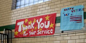 Signs in red, white, and blue adorn the walls of the gymnasium at Edison Intermediate School during its annual Veterans Day assembly.