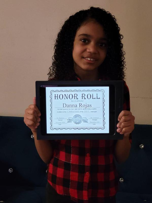 Danna holding honor roll certificate