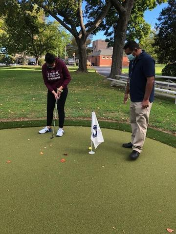 A student is putting on the green of a golf course as a teacher watches