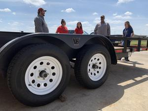 a group of girls standing next to a trailer they built talking to their teacher and a man from the maintenance department