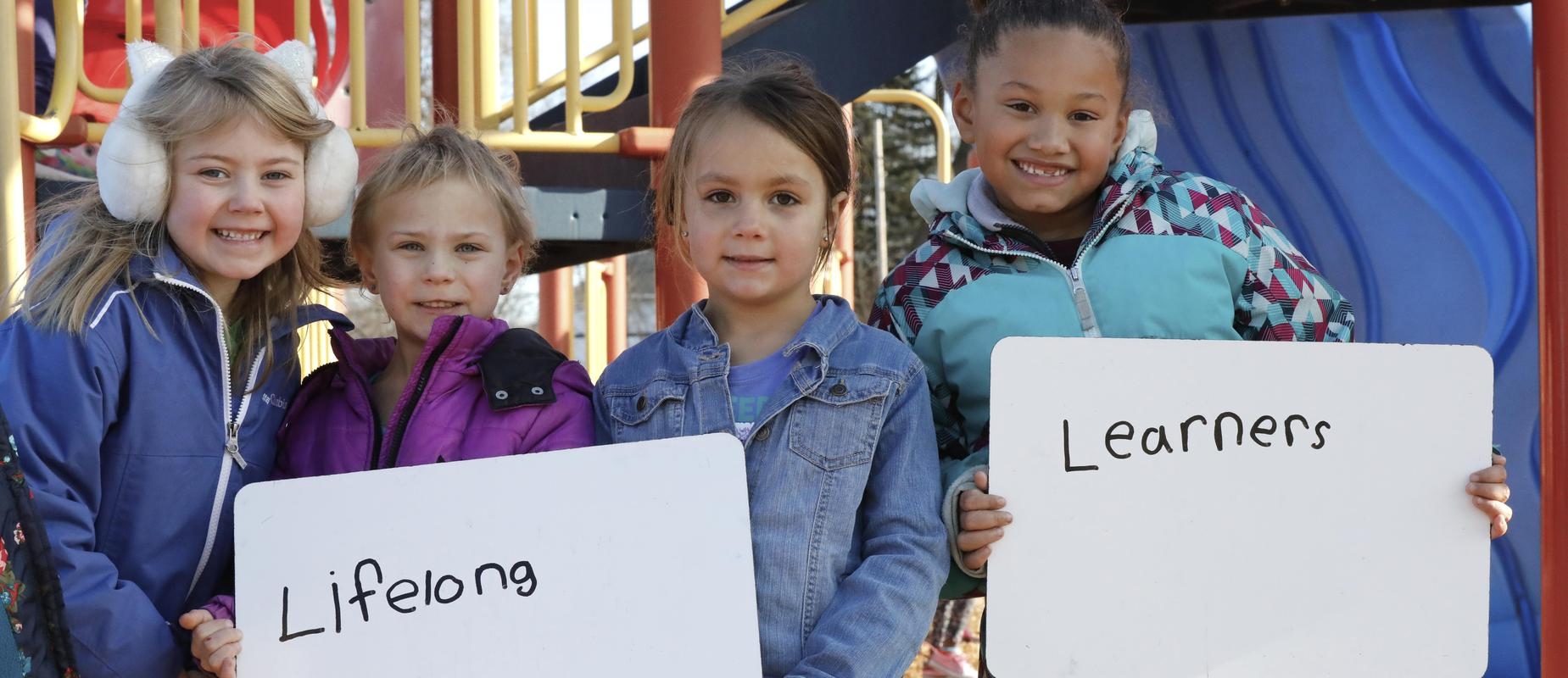 4 girls holding sign that says lifelong learners outside