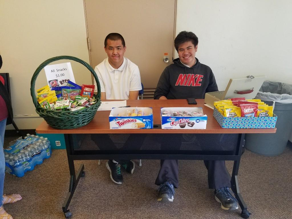 Students sitting at a table selling snacks