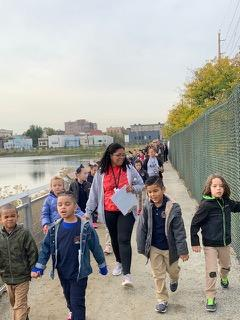 children walking side by side with their teacher on walking path of the viaduct