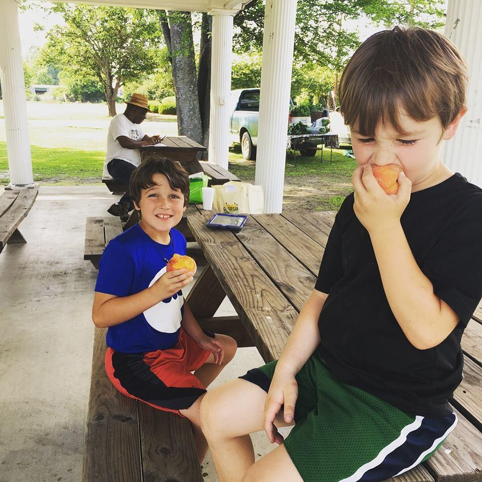 Two boys enjoying some peaches