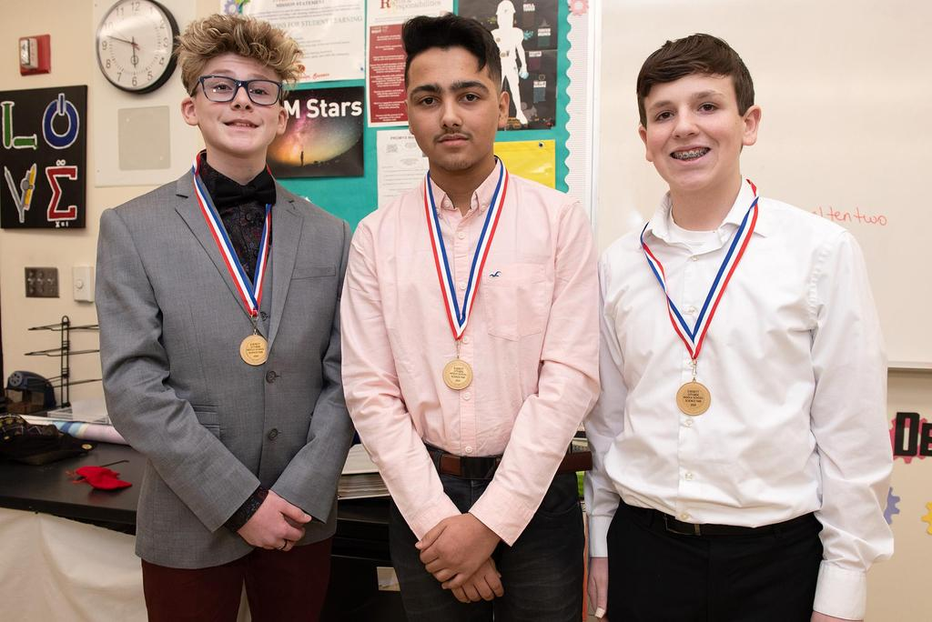 Three students wearing their honorable-mention medals