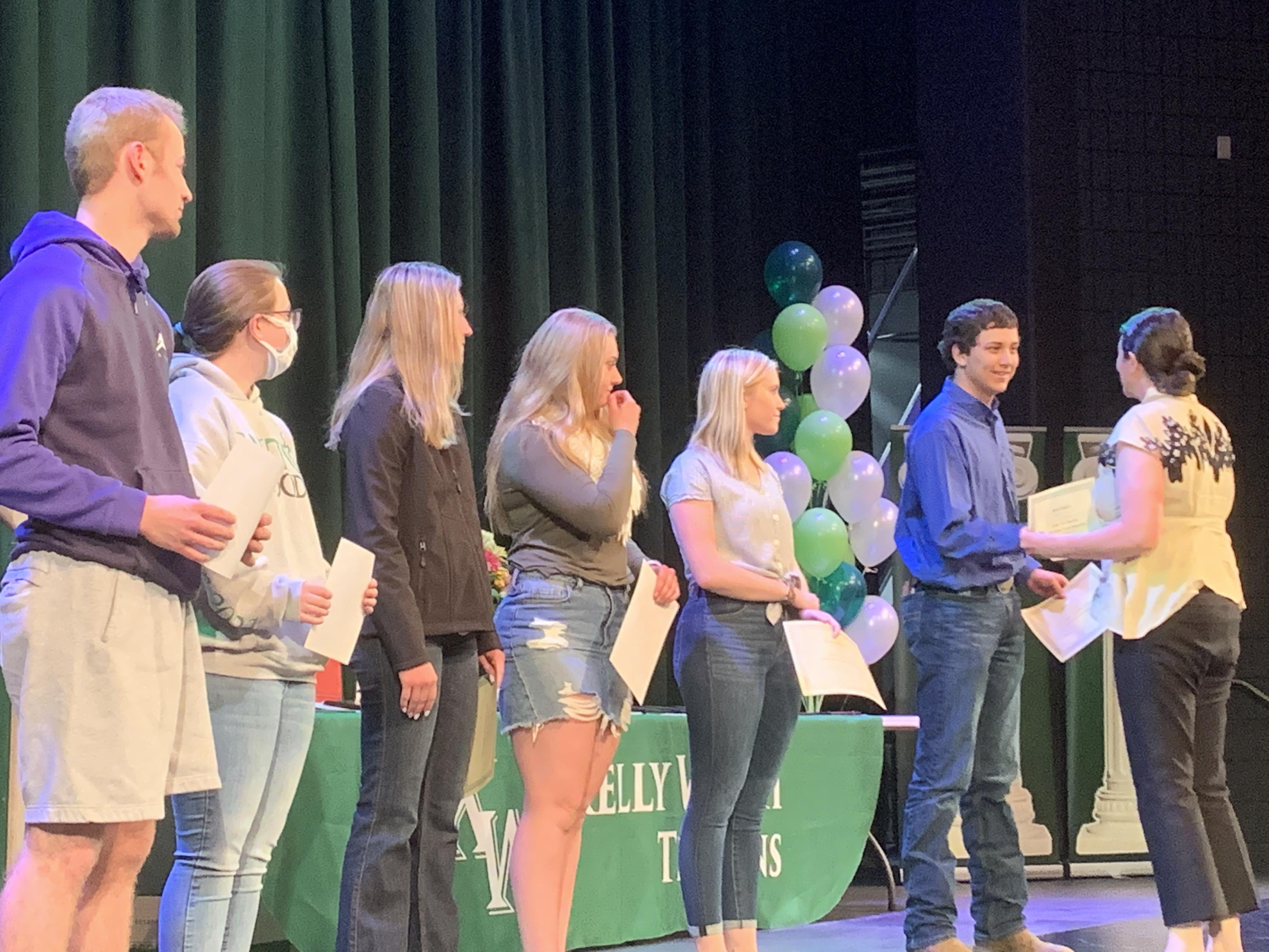 students receiving scholarship certificates