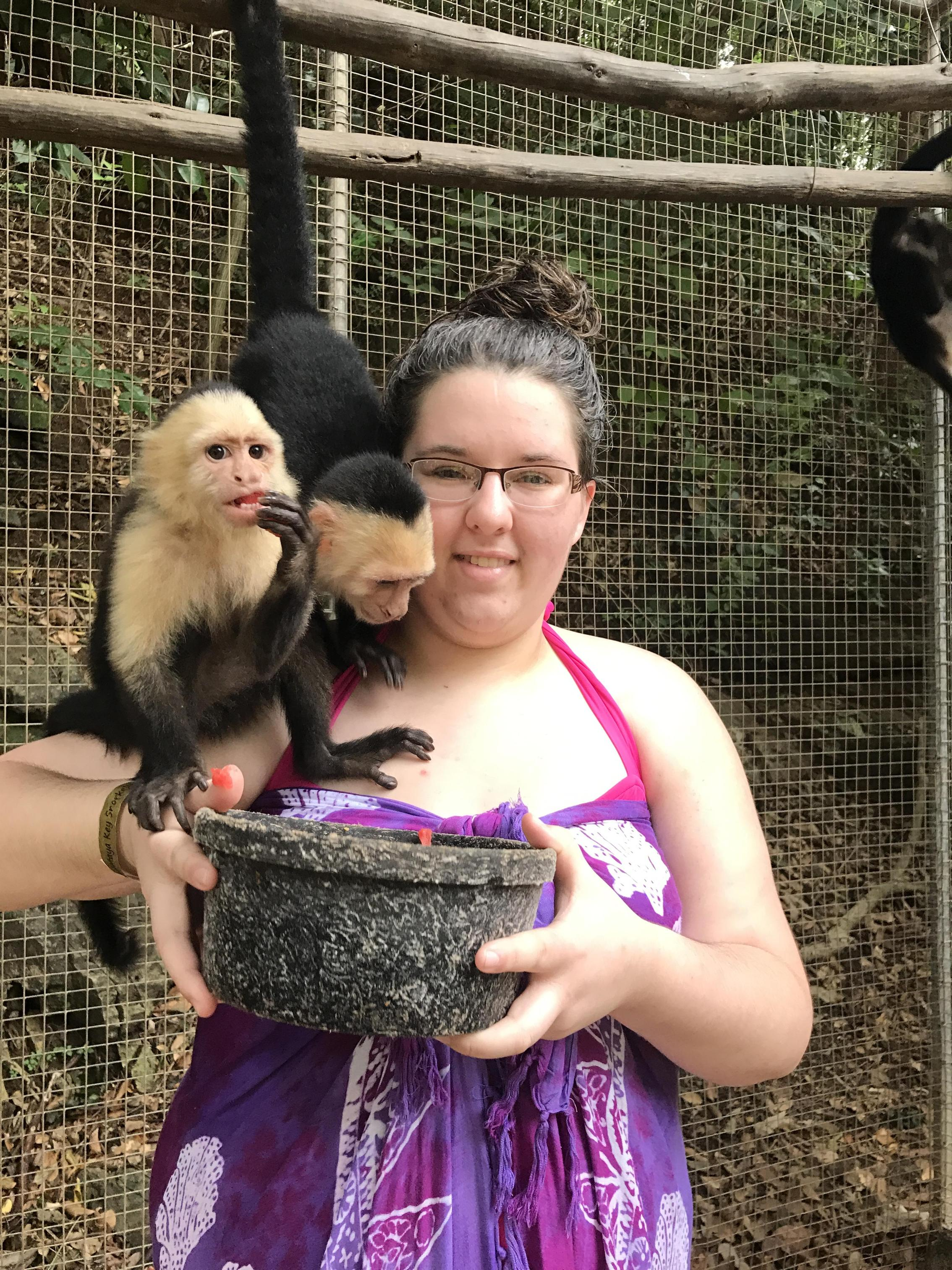 Ms. Butler with two monkeys on her shoulder eating food out of a bucket she's holding in an Animal Conservatory in Mahogany Bay, Roatán, Honduras in January 2017