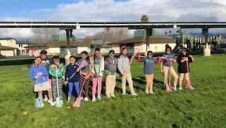 The girls lacrosse team pose with their equipment on the field