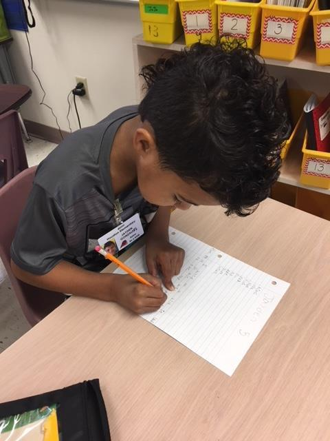 A student taking a spelling test, making sure he has a finger space in between his words.