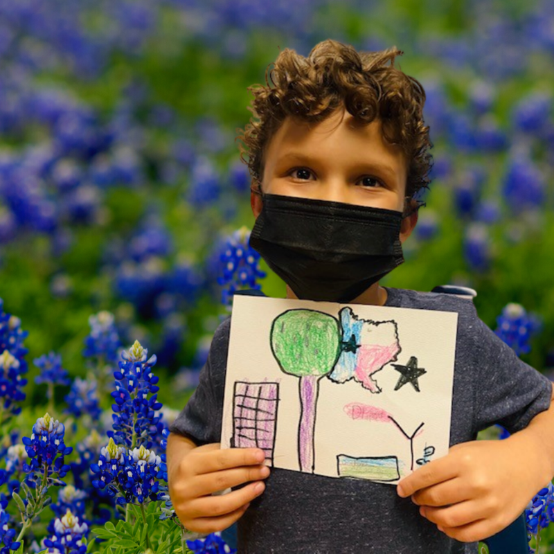 boy holding his artwork in front of bluebonnets