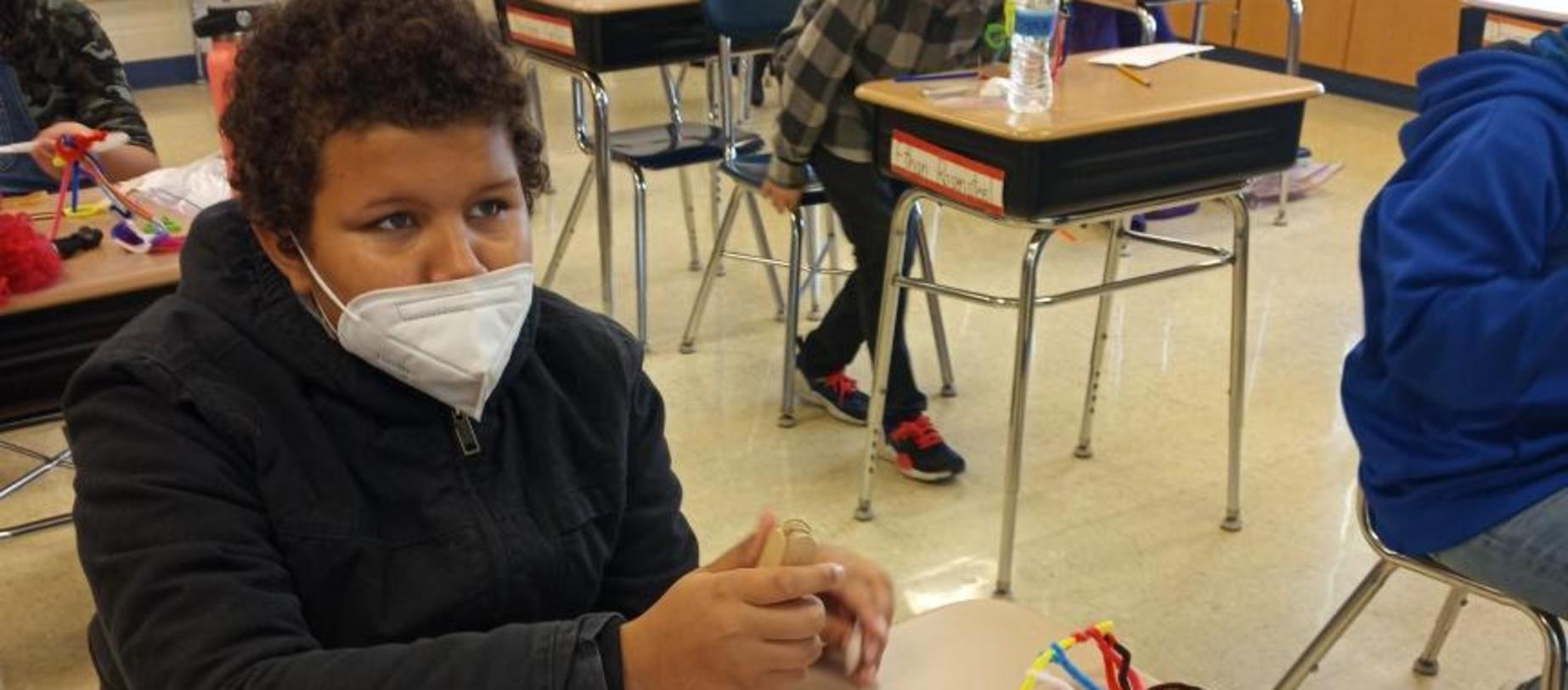 student wearing mask working on projects
