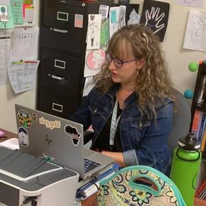 A teacher instructs via her laptop.