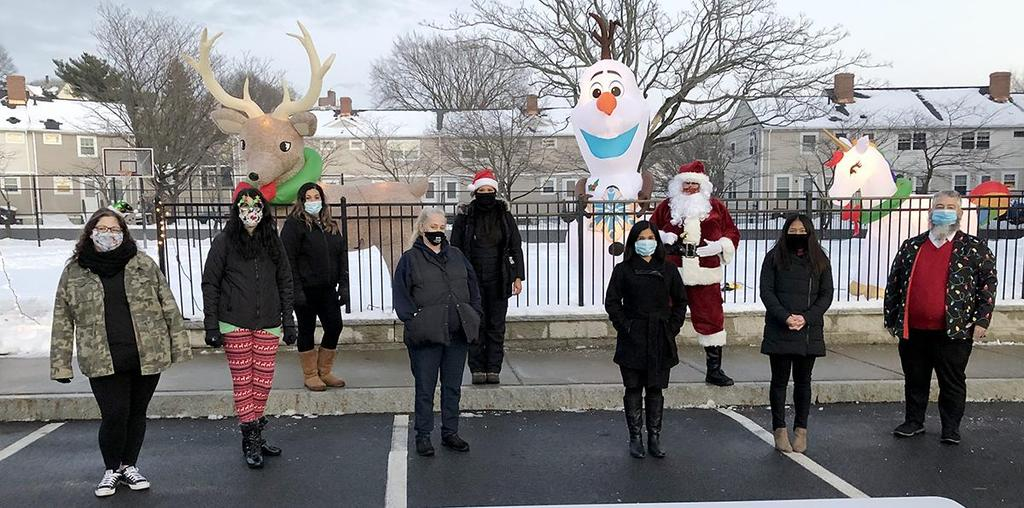 A group of adults, standing in front of inflatable holiday decorations