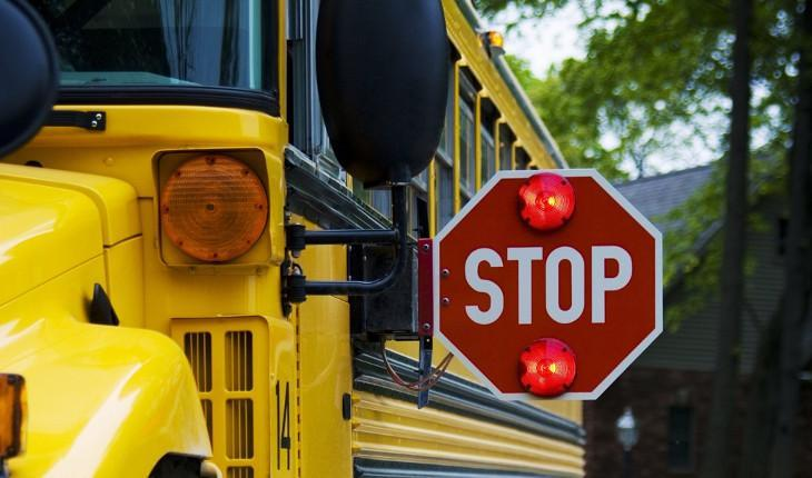 Photo of the front of a school bus with a red stop sign extended
