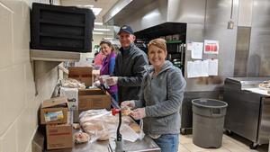 Three workers prepare meals