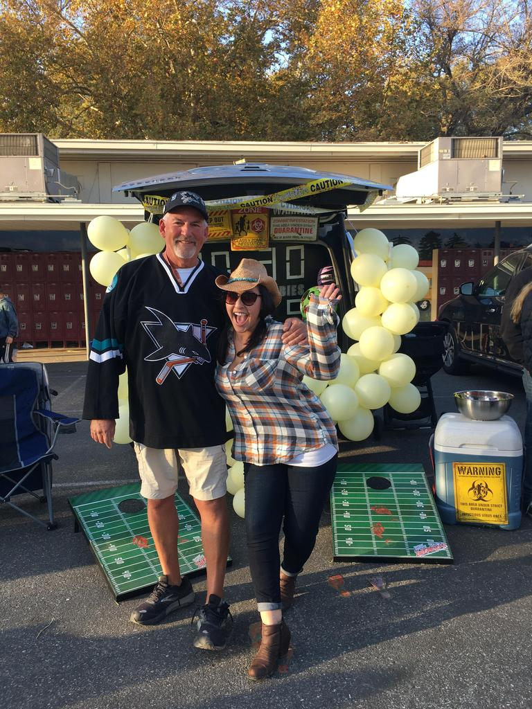 Adults dressed up as Sharks player and cow girl