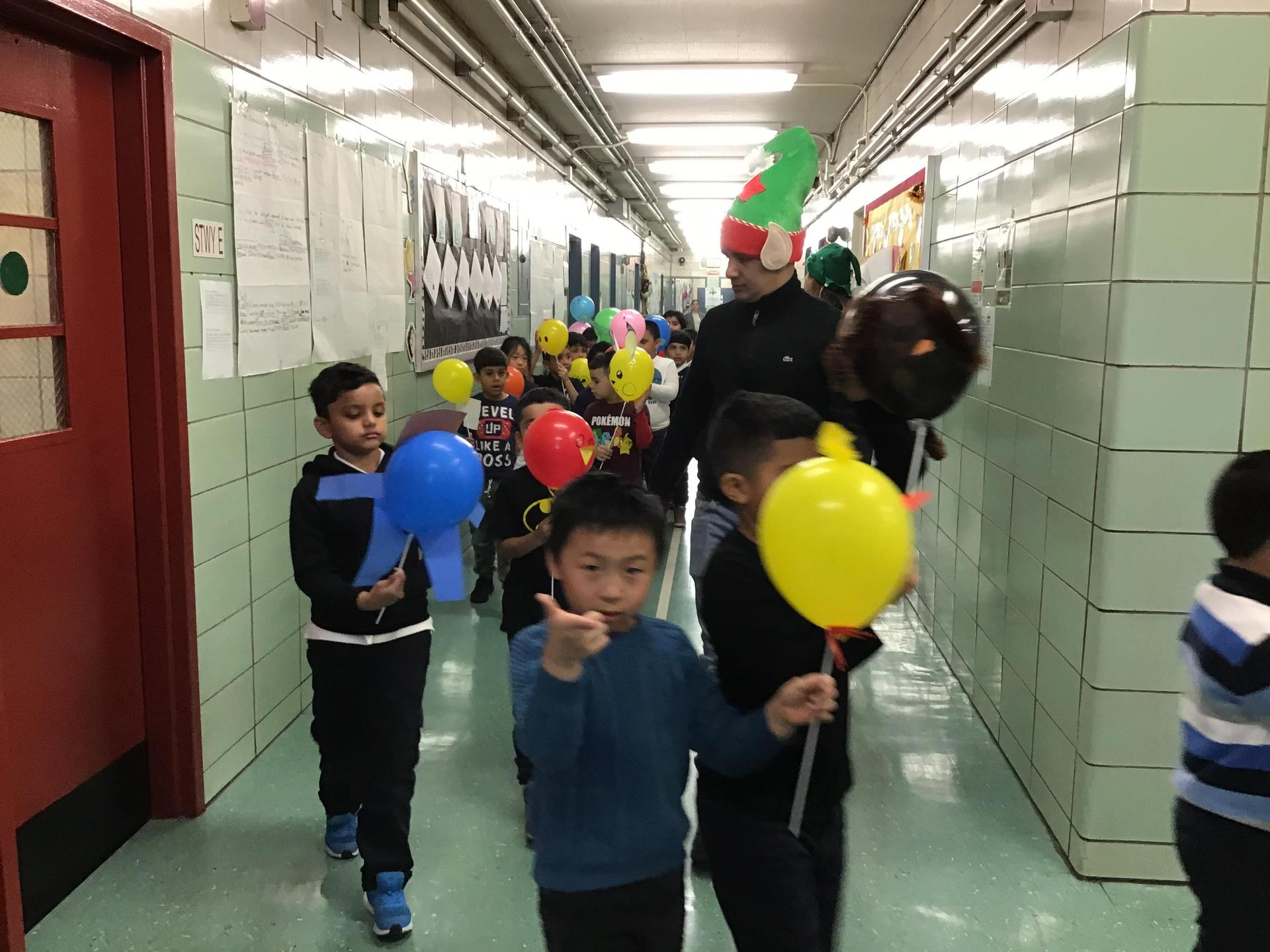 students and teachers parading in school hallway with balloons and signs